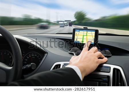 Close-up Of A Person's Hand Using Gps Navigation System In Car - stock photo