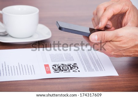 Close-up Of A Person Scanning Barcode Using Cellphone - stock photo