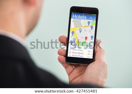 Close-up Of A Person Searching Hotels Using GPS Map With Navigation Pointers On His Smartphone
