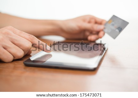 Close up of a person typing on a digital tablet device and holding a credit card while shopping online - stock photo