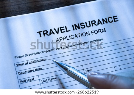Close-up Of A Person With Pen Filling Travel Insurance Application Form - stock photo
