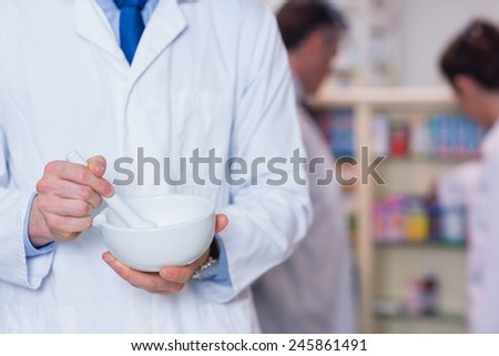 Close up of a pharmacist using mortar and pestle in the pharmacy - stock photo