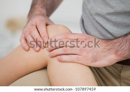 Close-up of a physiotherapist massaging a knee in a room - stock photo