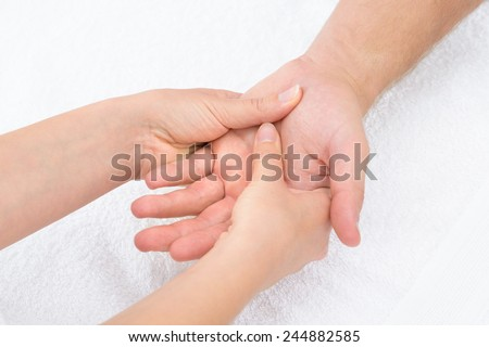Close-up Of A Physiotherapist Massaging Palm Of A Man - stock photo