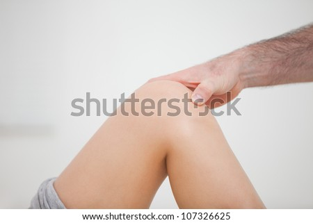 Close-up of a physiotherapist touching a knee in a room - stock photo