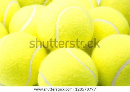 Close up of a pile of bright yellow tennis balls - stock photo