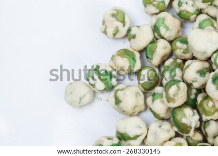 Close up of a pile of coated green peas. - stock photo