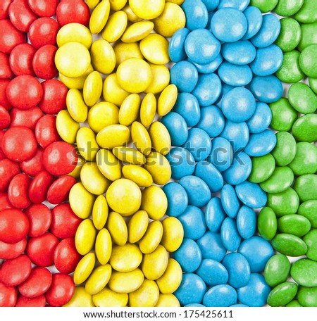 Close up of a pile of colorful chocolate coated candy by color in a row - stock photo