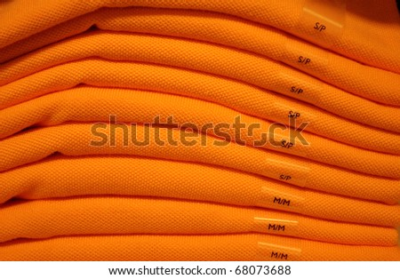 Close-up of a pile of orange T-shirts lying on a shelf of a mall