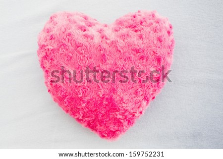 Close-up of a pink heart shaped pillow against white background - stock photo