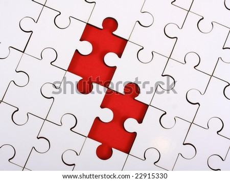 Close up of a plain white jigsaw puzzle with two pieces missing, which show as red gaps. - stock photo