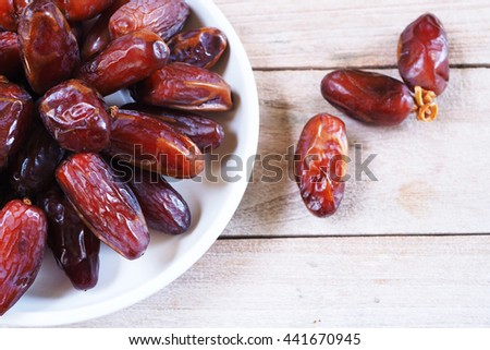 Close up of a plate of dried dates on a wooden background. Selective focus.