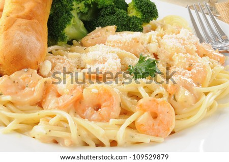 Close up of a plate of shrimp scampi in garlic butter sauce with bread sticks - stock photo