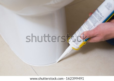 Close up of a plumber fixing toilet in a washroom with silicone cartridge - stock photo