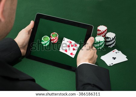 Close-up Of A Poker Hand With Digital Tablet Showing Chips And Cards - stock photo