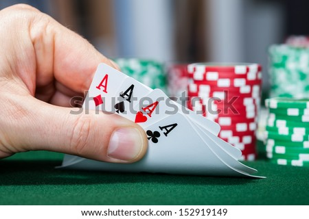 Close-up of a poker player holding playing cards