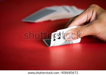 Close up of a poker player holding playing cards on red table. - stock photo