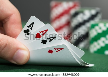 Close-up Of A Poker Player Playing Cards - stock photo