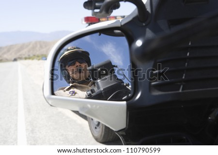 Close-up of a police officer reflecting in side view mirror - stock photo