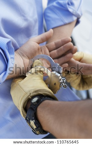 Close-up of a policeman arresting criminal - stock photo