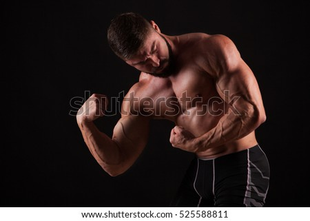 Close-up of a power fitness man's hand. Strong handsome young bodybuilder demonstrate his muscles and biceps
