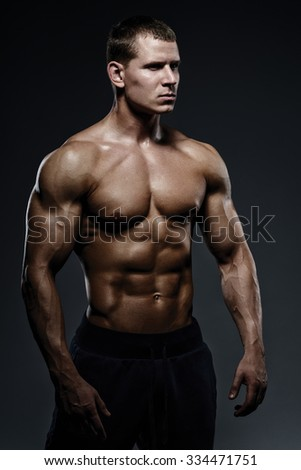 Close-up of a power fitness man. Strong and handsome young man with muscles and biceps. Studio shooting on black background. - stock photo
