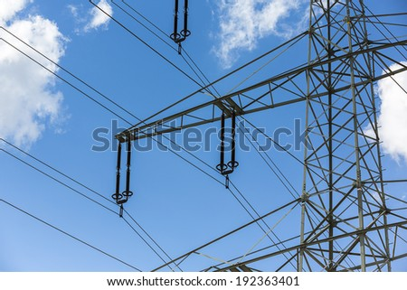 close-up of a Power line on blue sky with clouds energy electricity  - stock photo