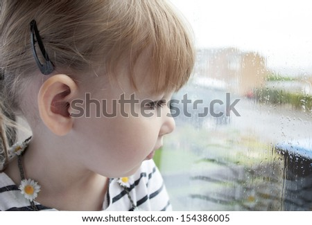 close up of a preschool girl looking out of a rain covered window