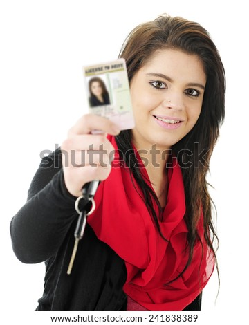 Close-up of a pretty teen girl happily holding up her new driver's license for the viewer to see, along with a car key.  Focus on teen.  On a white background. - stock photo
