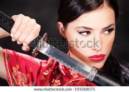 Close up of a pretty woman and katana - stock photo