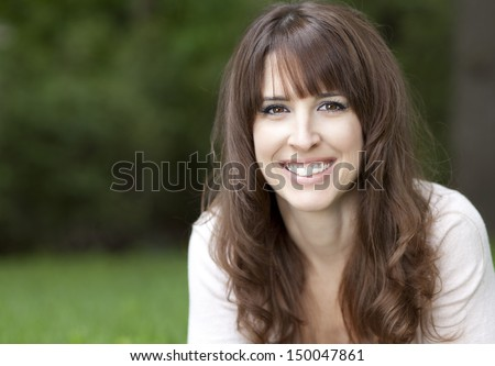 Close-up of a pretty woman on the grass smiling - stock photo