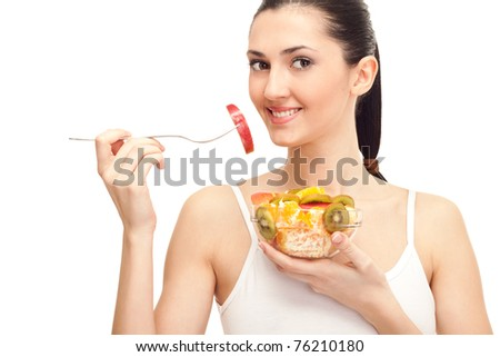 close up of a pretty young lady eating fruit salad, isolated on white - stock photo