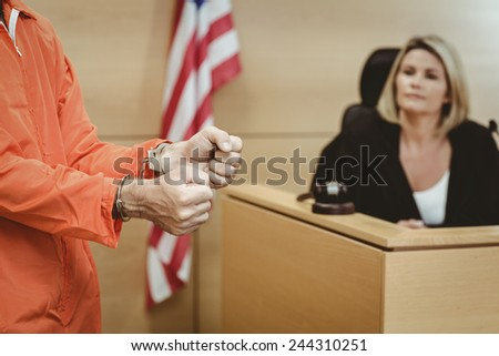 Close up of a prisoner wearing handcuffs in the court room - stock photo