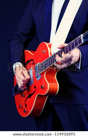 Close-up of a professional artist playing on guitar. Over black background. - stock photo