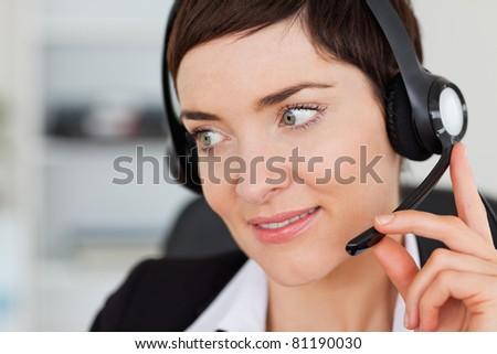 Close up of a professional secretary calling with a headset in her office - stock photo
