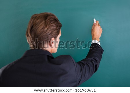 Close-up Of A Professor Writing On Chalkboard - stock photo