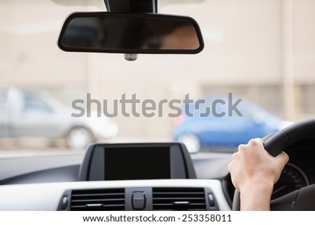 Close up of a rear view mirror in her car - stock photo