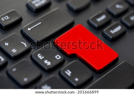 Close up of a red blank return key on a black computer keyboard