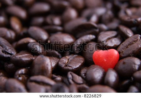 Close up of a red candy heart in coffee beans