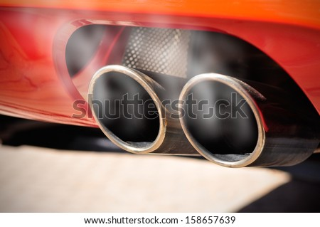 Close up of a red car dual exhaust pipe with smoke around it - stock photo
