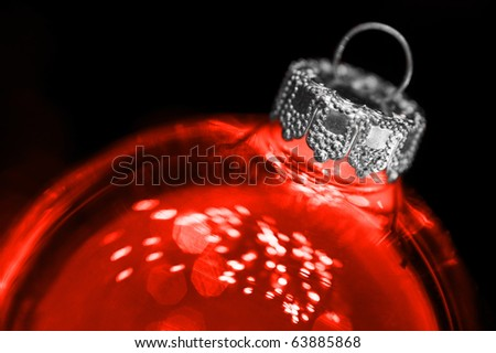close-up of a red glass christmas bauble on black - stock photo