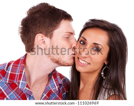 Close-up of a red-haired young man kissing his girlfriend on her cheek - stock photo