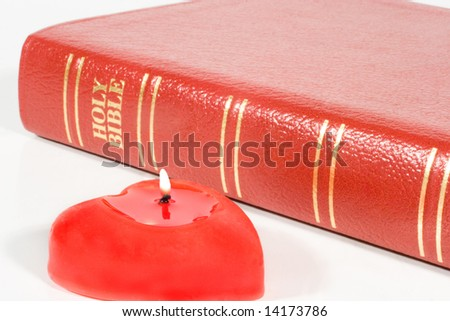 Close-up of a red heart-shaped candle and Holy Bible - stock photo