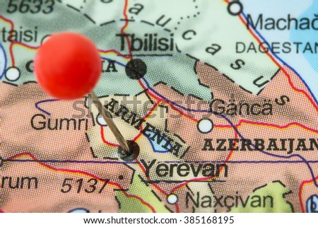 Close-up of a red pushpin in a map of Yerevan, Armenia. - stock photo