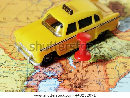 Close-up of a red pushpin on a map of Kenia  Africa and a taxi car - travel concept - stock photo
