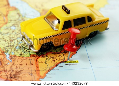 Close-up of a red pushpin on a map of Mogadishu, Somalia Africa and a taxi car toy - travel concept - stock photo