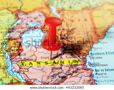 Close-up of a red pushpin on a map of  Tansania  Africa - travel concept - stock photo