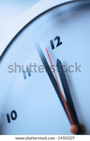 Close up of a red second hand approaching midnight on a wall clock - stock photo