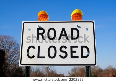 Close up of a road closed sign and warning signals