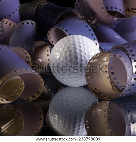 Close-up of a roll 35 mm photographic films and golf ball - stock photo